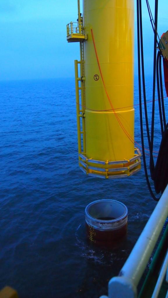 Zusammensetzen von Transition Piece (gelb) und Mono Pile zum Fundament für die Windenergieanlage